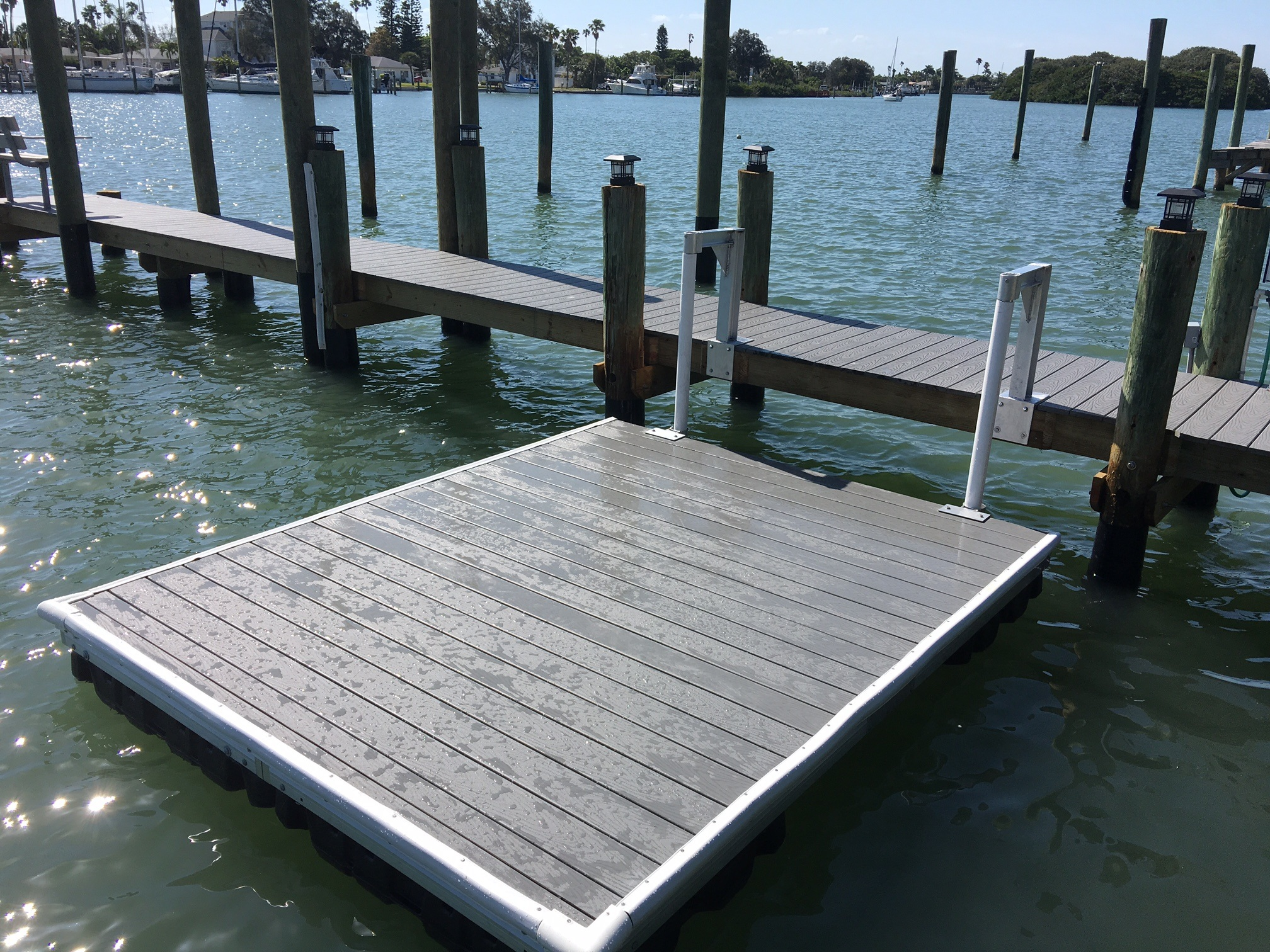 Composite Trex floating dock with pipe slides attached to stationary dock on the water